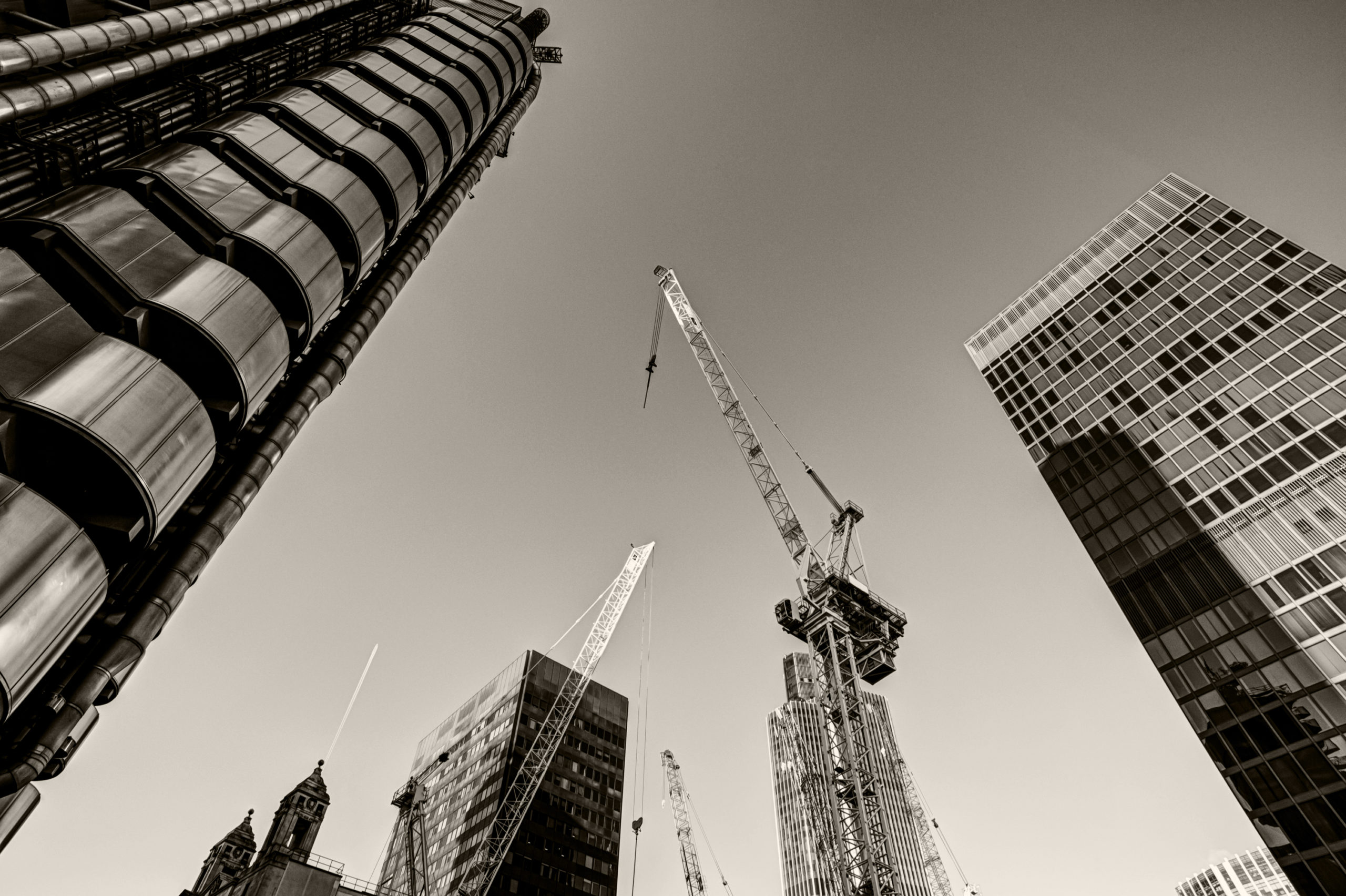 Upward angle looking at tall buildings and cranes